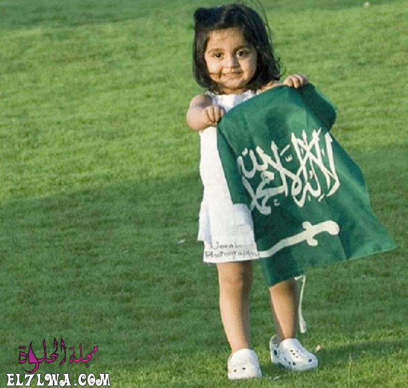 صورة طفلة سعودية تمسك بالعلم السعودي